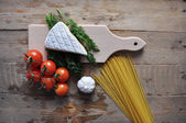 Brie cheese on a board with spaghetti and tomato on wood background — Stock Photo