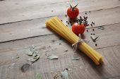 Cooking concept. Uncooked italian pasta: vermicelli, spaghetti with twine and tomato on wooden background — Stock Photo