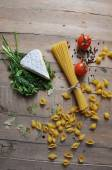 Brie cheese with herbs dill and parsley with different types of spaghetti noodles — Stock Photo