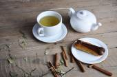 Exquisite cream dessert eclair sprinkled with chocolate and tea on the wood — Stock Photo