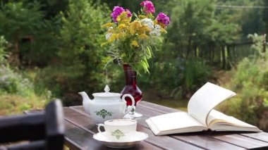 Tea table with a book and flowers — Stock Video