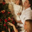 Young family decorating the Christmas tree — Stock Photo #60152251