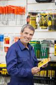 Worker Holding Tool Package In Hardware Shop — Stock Photo