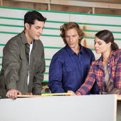 Carpenters Communicating At Table In Workshop — Stock Photo