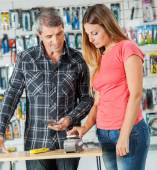 Couple Paying For Tools Through Smartphone In Store — Stockfoto