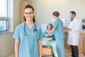 Nurse Smiling With Patient And Medical Team In Background — ストック写真