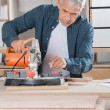 Carpenter Using Power Tool On Wood In Workshop — Stock Photo #54521335