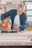 Carpenter Using Power Tool On Wood In Workshop — Foto de Stock