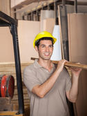Carpenter Carrying Plank While Looking Away — Stock Photo