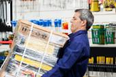 Worker Lifting Heavy Tool Package In Hardware Shop — Stock fotografie