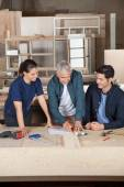 Carpenter Drawing Blueprint With Team At Workbench — Stock Photo