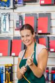 Saleswoman Holding Air Compressor Hose In Store — Stock fotografie