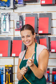 Saleswoman Holding Air Compressor Hose In Store — Stock Photo