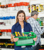 Woman Carrying Basket Full Of Tools In Store — Foto de Stock