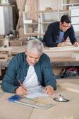 Senior Carpenter Working On Blueprint In Workshop — Stock Photo