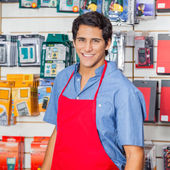 Handsome Salesman In Red Apron Smiling At Hardware Shop — Stock Photo