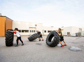 Athletes Doing Tire-Flip Exercise Outdoors — Stock Photo