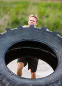 Athlete Lifting Large Tractor Tire — Stock fotografie