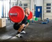 Male Athlete Lifting Barbell At Gym — Stockfoto