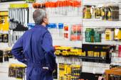 Worker With Hands On Hip In Hardware Store — Stock Photo