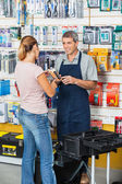 Salesman Showing Flashlight To Customer In Hardware Store — Foto Stock