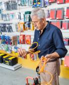 Man Analyzing Air Compressor Hose In Shop — Stock Photo