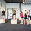 Постер, плакат: Athletes Practicing Box Jumps