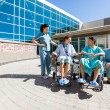 Patients On Wheelchair By Nurses Outside Hospital Building — Stock Photo #54600769