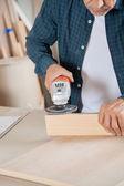 Senior Zimmermann mit elektrischen Sander auf Holz — Stockfoto