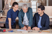 Carpenter Drawing Blueprint With Team At Table — Stock Photo