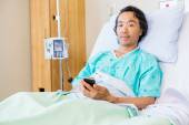 Patient Holding Mobile Phone While Resting On Hospital Bed — ストック写真