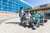Patients On Wheelchair By Nurses Outside Hospital Building — Stock Photo
