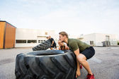 Fit Athletes Doing Tire-Flip Exercise — Stockfoto