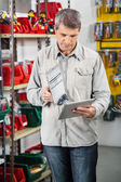 Man Checking Product Through Digital Tablet — Stock Photo