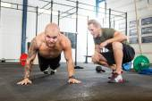 Trainer Assisting Man In Doing Pushups — Stock Photo