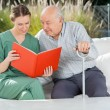 Senior Man Reading Book With Female Caretaker On Couch — Stock Photo #55487523