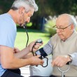 Doctor Measuring Blood Pressure Of Senior Man — Stock Photo #55489707