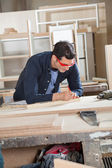 Carpenter Measuring Wood At Workbench — Stock Photo