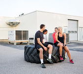 Fit Friends Conversing While Relaxing On Tire — Stock Photo