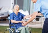 Caretaker Helping Senior Woman To Get Up From Wheelchair — Stock Photo