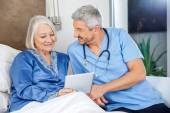 Happy Caretaker With Senior Woman Using Digital Tablet — Stock Photo