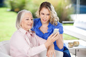 Granddaughter Assisting Granddaughter In Using Smartphone — Foto Stock