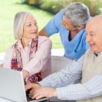 Caretaker Looking At Senior Woman By Man Using Laptop — Stock Photo #55490779