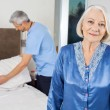 Senior Woman With Caretaker Making Bed At Nursing Home — Stock Photo