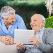 Male Caretaker And Senior Man Laughing While Using Tablet Comput — Stock Photo #55500589