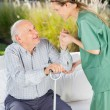 Female Nurse Helping Senior Man To Get Up From Couch — Stock Photo #55503063