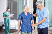 Happy Male Caretaker Helping Senior Woman In Walking — Stock Photo