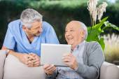 Male Caretaker And Senior Man Laughing While Using Tablet Comput — Stock Photo