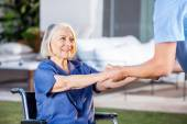 Male Nurse Helping Senior Woman To Get Up From Wheelchair — Stock Photo