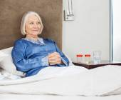 Smiling Senior Woman Relaxing On Bed At Nursing Home — Foto Stock